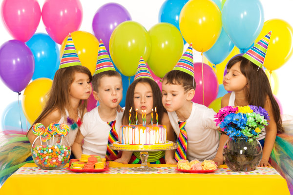 Group of joyful little kids celebrating birthday party and blowing candles on cake. Holidays concept.